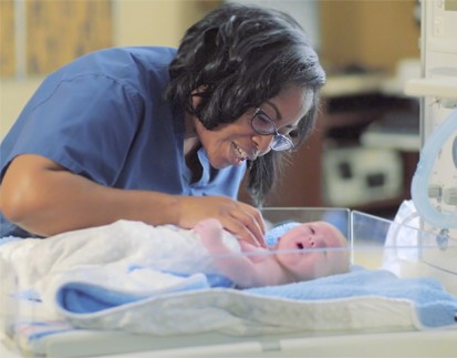 Nurse with baby in warmer